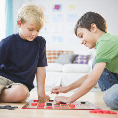 Boys sitting on floor playing checkers