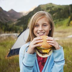 Caucasian girl eating cheeseburger at campsite