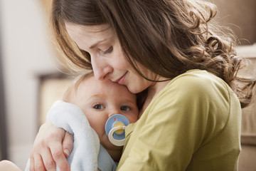 Caucasian baby boy with pacifier in mother's arms