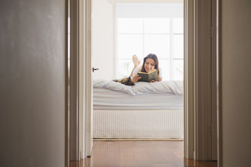 Hispanic woman laying in bed reading book