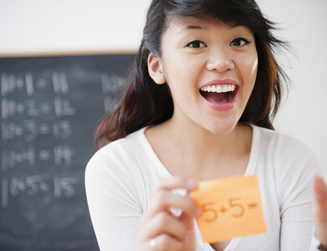 Pacific Islander teacher holding sticky note with math problem