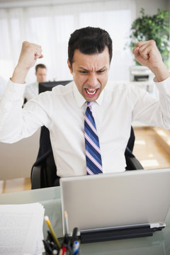 Angry mixed race businessman shouting in laptop