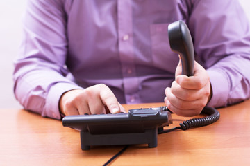 Businessman dials the number on the office phone