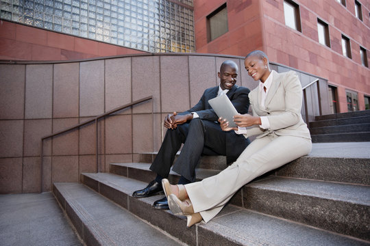 Business people sitting in stairs using digital tablet