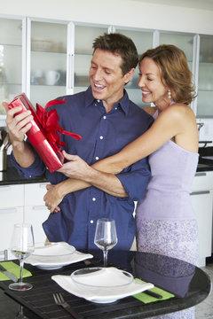 Caucasian woman giving husband a gift