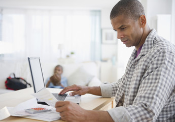 Mixed race man paying bills online