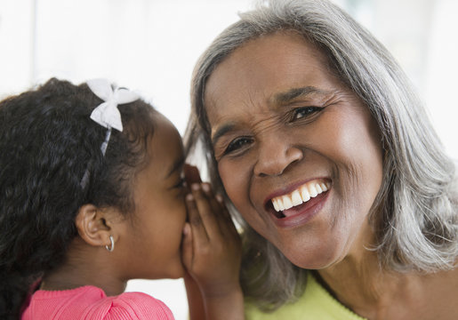 African American girl telling secret to grandmother
