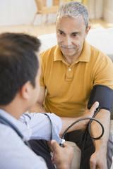Hispanic man having his blood pressure taken