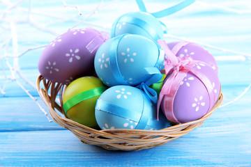 Easter eggs in basket, on blue wooden background