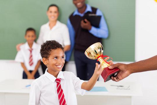 school boy receiving a trophy in classroom