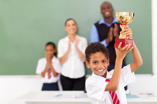 elementary school student holding a trophy