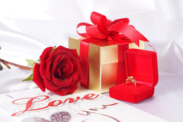 Golden diamond ring with gift box and red rose