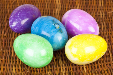 Easter eggs in different colors on the braided surface