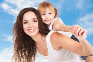 Happy mother and daughter playing on sky background