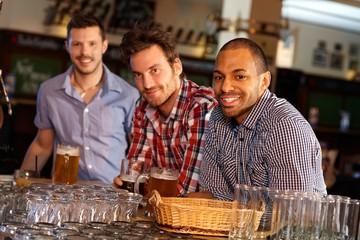 Young men drinking beer at bar counter