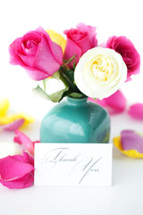 bouquet of colorful roses in vase,petals and card with the words