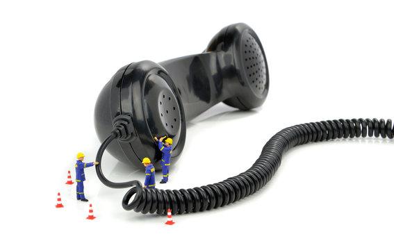 Telephone engineers repairing a telephone receiver