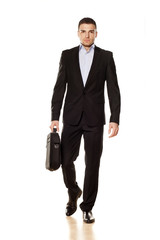 attractive young businessman walking with a laptop bag