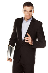 smiling young businessman with folder in hand pointing a finger