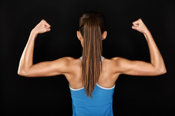 Strong fitness woman showing back biceps muscles