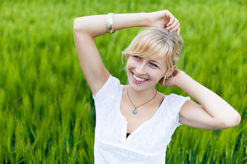 lächelnde junge frau steht im kornfeld