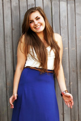 Beautiful girl smiling on background of the wall .