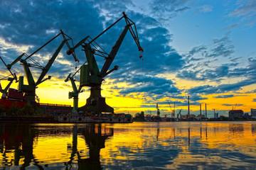Obraz Monumentalne żurawie o zachodzie słońca w Stoczni Gdańskiej - fototapety do salonu