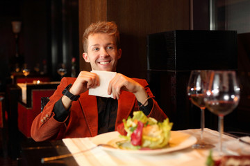Happy young man in a red suit holding a napkin