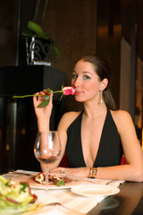 beautiful woman in a black dress with a rose