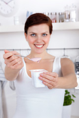 beautiful woman offering yogurt as breakfast or snack