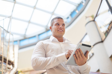 Good looking Young Businessman with tablet computer in modern bu