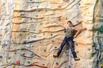 man on rock wall in sport center