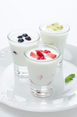 three yogurt with fruit in a glass beaker vertical closeup