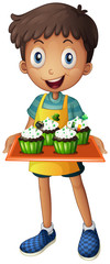 A young boy holding a tray with cupcakes