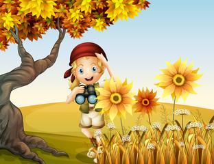 A girl holding a telescope near the sunflowers