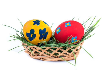 two Easter eggs in a basket on a white background