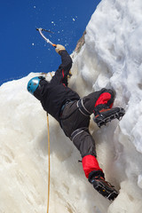 Ice climber in action on top of cliff