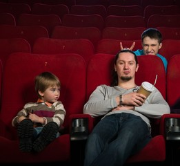 Man with boy in cinema with funny guy behind them
