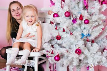 The little girl with ðîäèòåëÿìèó a white Christmas fir-tree