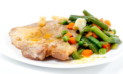 Fried pork meat with vegetables on white plate.
