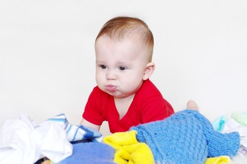 Рuzzled baby among a kidswear