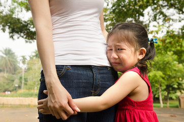 little asian girl crying and hugging her mother