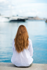 frau sitzt am hafen und schaut auf´s meer