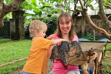 family touching monitor lizard