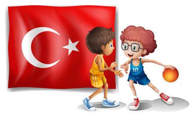 Two boys playing basketball in front of the flag of Turkey