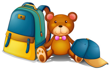 A backpack, a bear and a baseball cap