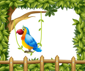 A parrot hanging in a vine plant near the wooden fence