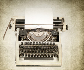 Antique typewriter on grunge background