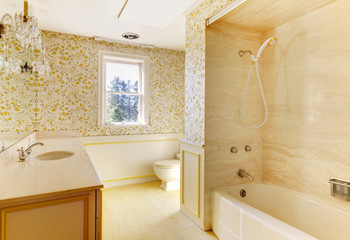 Old American house bathroom with wallpaper.