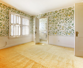 Old American house bedroom with wallpaper and carpet.